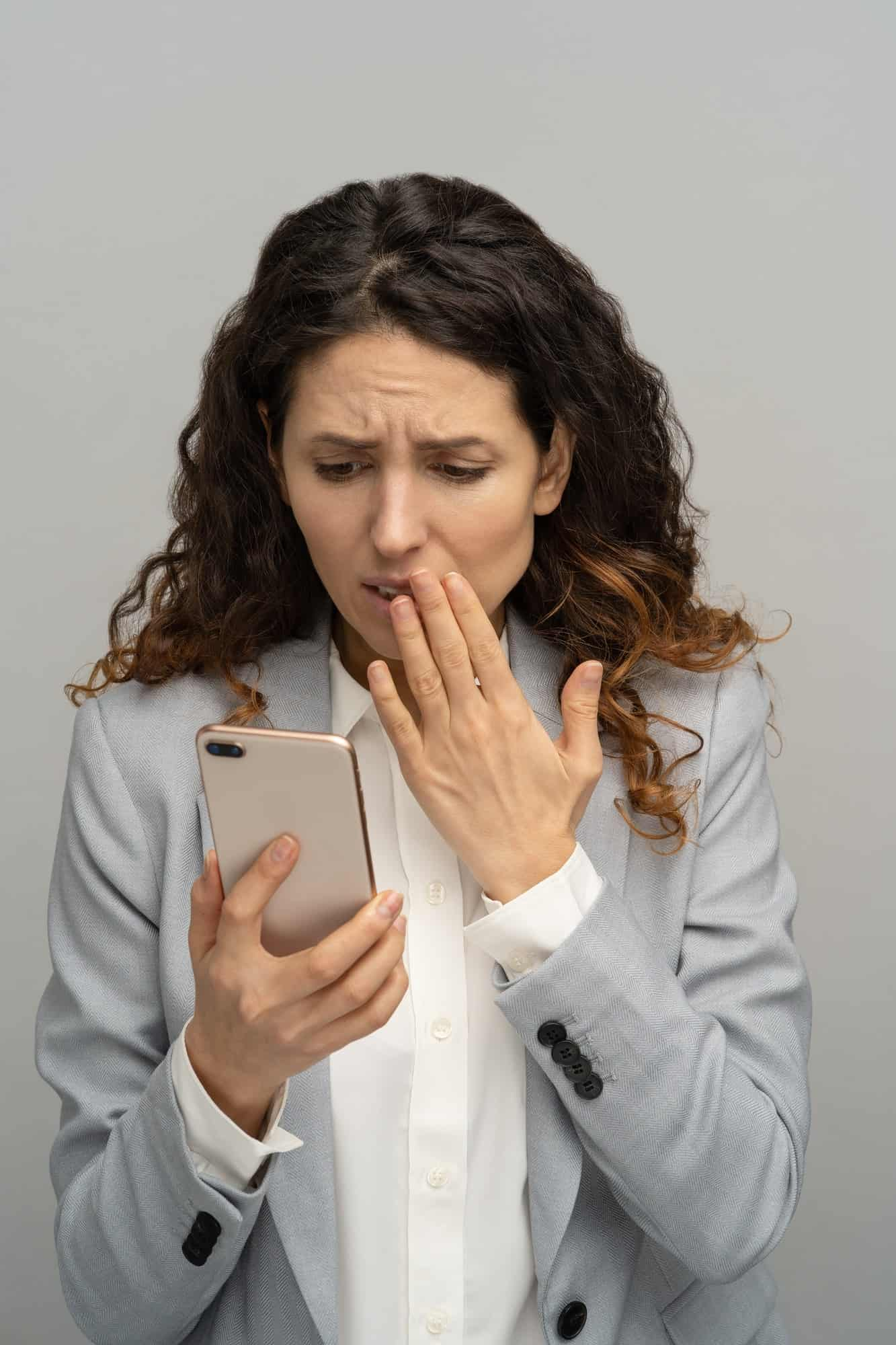 Frustrated shocked business woman or office worker looking at phone stunned with bad negative news