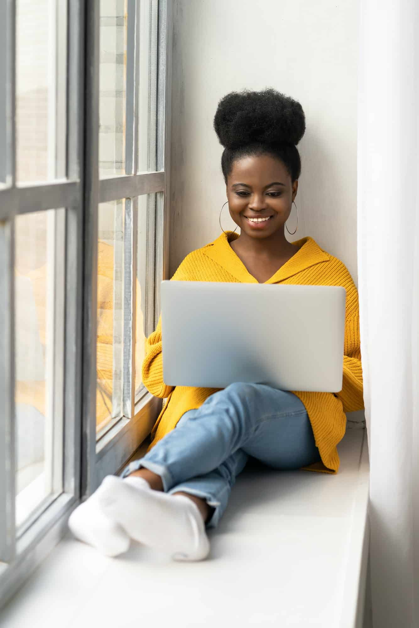 Smiling Black woman in yellow cardigan sitting on windowsill working on laptop talking in video chat