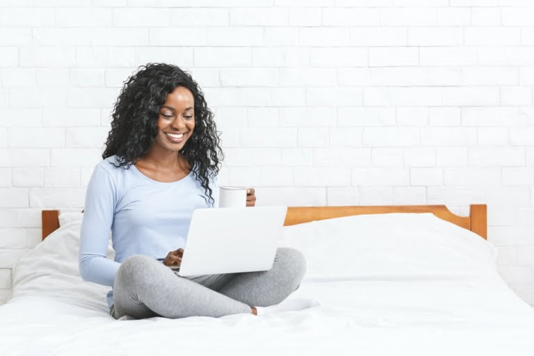 Beautiful smiling young woman sitting on bed, using laptop